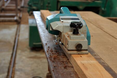 Front view of electric planer on the wooden plank in carpentry workshop Stock Photo