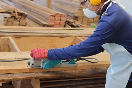 planos electricos: Carpintero que usa la cepilladora eléctrica con el tablón de madera en taller de carpintería. Él está usando equipo de seguridad Foto de archivo