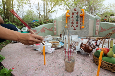 Ratchaburi, Thailand - April 4, 2017 : Thai people praying Ancestor Worshipping with Sacrificial offering in the Qingming Festival at Jing Gung Cemetery