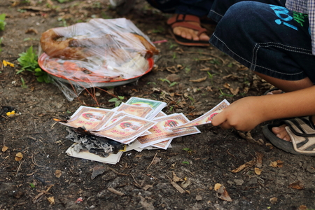 envelope: Ratchaburi, Thailand - April 4, 2017 : Burning of fake money made from paper materials during Chinese Qing ming Festival or Tomb Sweeping day in Jing Gung Cemetery.