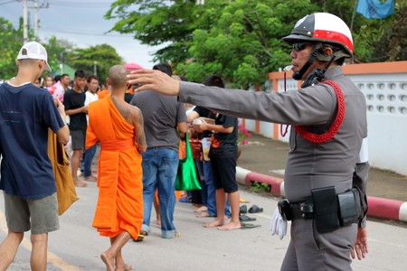 Ratchaburi, Thailand - October 18, 2016:Thai police support people and Buddhist monks in the end of Buddhist Lent Day. Zdjęcie Seryjne - 83898489