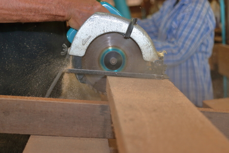 Hands of professional carpenter using circular saw cutting wooden board in wood workshop. Stock Photo