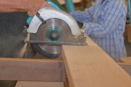Carpenter using circular saw cutting wooden board in wood workshop. Stock Photo