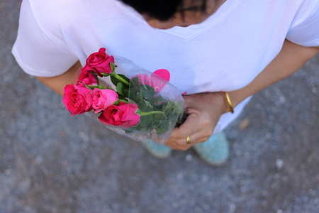 Top view of a beautiful bouquet of red roses is held by middle aged woman. Valentines day or ramantic love concept.