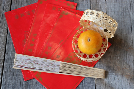 old envelope: Top view of orange in a basket on old wooden board with Chinese red envelope packet or ang pao and hand blow background. Happy Chinese new year concept.