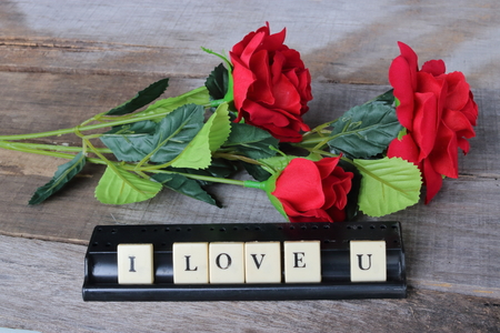 I love u wording by crossword on old wooden board with artificial red roses background. Love and romance Valentines day concept