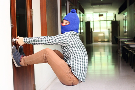 Masked burglar attempt to open the door before burglary. Criminal concept Stock Photo