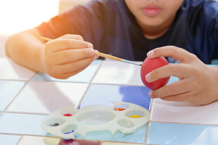 Hands of cute boy painting  egg with paintbrush for preparing Easter day. Sunshine effect