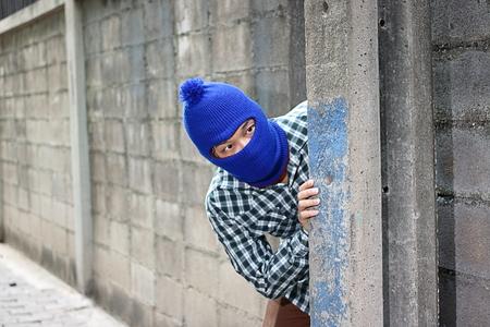 Masked burglar sneaking behind concrete pole before the burglary. Crime concept 版權商用圖片 - 84638967