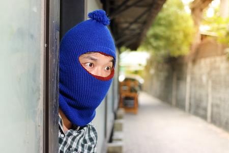 Burglar hiding behind entrance before burglary. Criminal concept