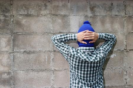 felonious: Burglar surrenders against brick wall background Stock Photo