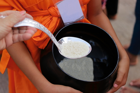 limosna: Hands of Thai people put food offering in Buddhist monks alms bowl in Songkran festival Day. Selective focus and shallow depth of field.