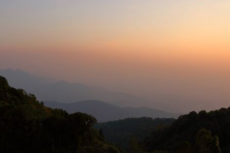 smoky mountains: Beautiful orange and yellow sunset and layers of silhouettes mountain in Chiang Mai , Thailand