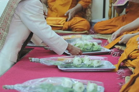 Unidentified people give the offering dedicated to the monks in temple Stock Photo