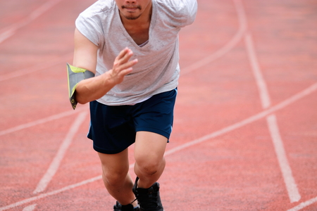 Runner athelete man running on the trackrace . Jogging for healthy concept Stock Photo