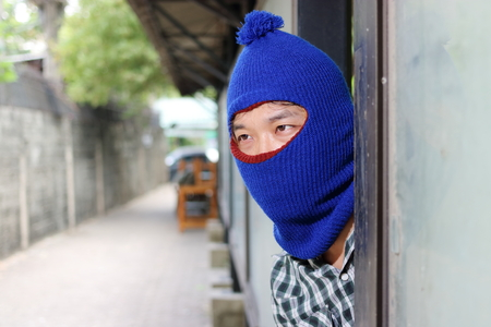 Masked burglar wearing a balaclava sneaking behind a pole before the burglary. Crime concept Stock Photo