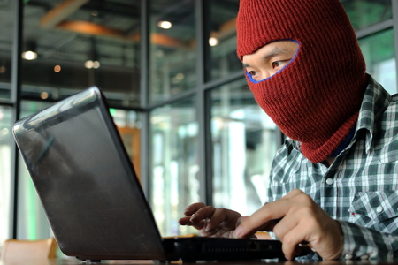 furtive: Masked hacker wearing a balaclava looking a laptop and stealing important information data. Network security and privacy crime concept. Stock Photo