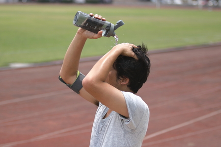 Gezond jong Aziatisch agent gietend water met waterbottle op zijn gezicht na het lopen op spoor in stadion. Stockfoto