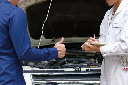 メカニックと顧客自動サービスのガレージで車のエンジンを修理の間。