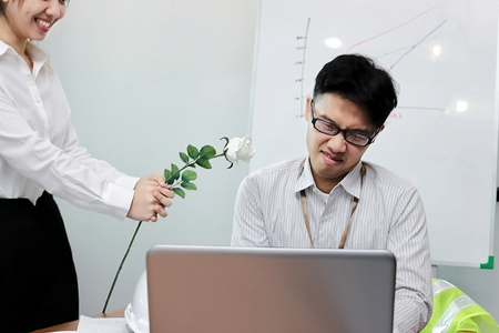 Angry Asian business man refuses a white roses from beauty woman.