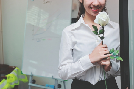 Vintage toned image of cheerful young Asian business woman holding a white roses in office on Valentines day. Love and romance in workplace concept.