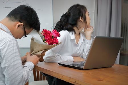 Angry Asian woman refuses a bouquet of red roses from business man in office. Disapointed love concept. Imagens