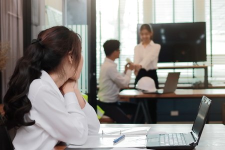 Envious angry Asian business woman looking affectionate couple in love in office. Jealousy and envy in friend relationship Stock Photo