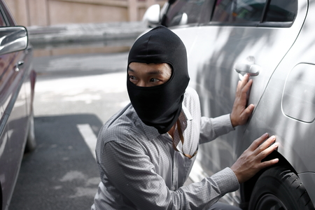 Masked burglar wearing a balaclava ready to burglary against car background. Insurance crime concept.