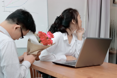 Angry Asian woman refuses a bouquet of red roses from business man. Disappointed love concept. Stock Photo