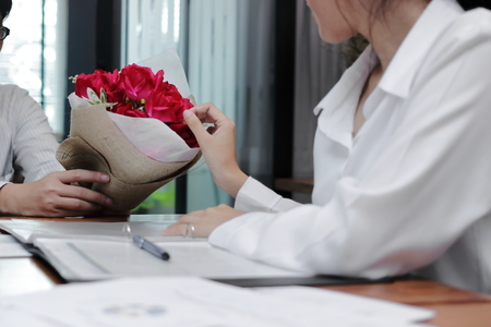 Vintage toned image of attractive young Asian woman accepting a bouquet of red roses from boyfriend in office on valentines day. Love and romance in workplace concept.