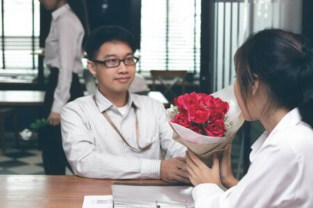 Vintage toned image of cheerful young Asian woman accepting a bouquet of red roses from boyfriend with envious angry woman background on valentine's day. Love and romance in workplace concept.