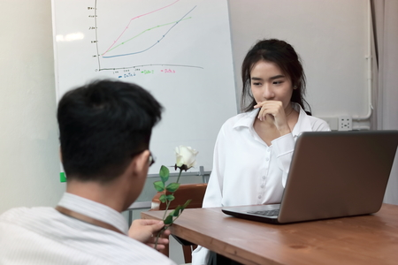 Surprised young Asian business woman excited to get a white rose in office on valentine's day. Love and romance in workplace concept.