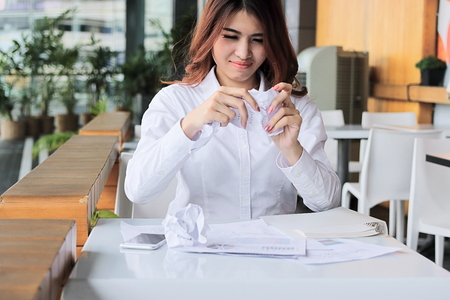 Frustrated young Asian employee holding crumpled paper and feeling stress against her job in office. Standard-Bild