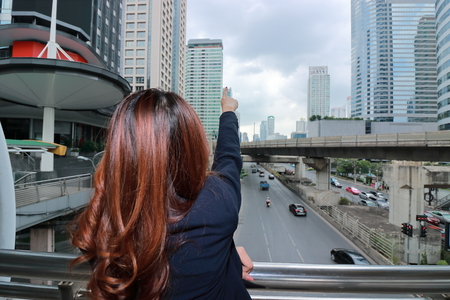 Wide angle shot of back view of young Asian business woman pointing finger at urban building far away background.