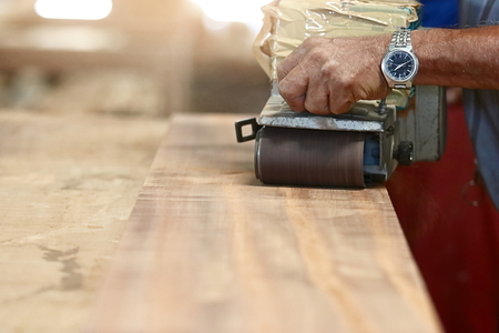 Front view of belt sander working on a piece wood with hands of worker with copy space. Selective focus and shallow depth of field. Stock Photo