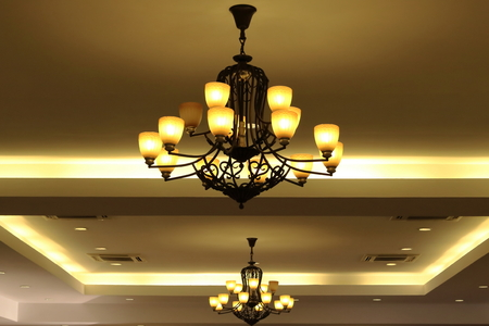 Luxury yellow chandelier hanging under ceiling in the room.