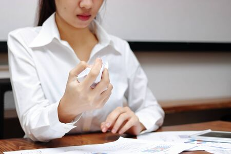 Selective focus on hands of young Asian business woman holding crumpled paper and feeling stress against her job in office. Stock Photo