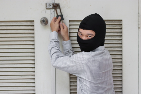 Masked robber using a lock picking tool to breaking and entering into a house. Criminal crime concept.
