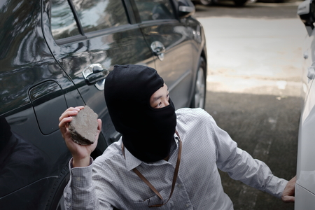 Masked burglar wearing a balaclava holding little stone ready to burglary against car background. Insurance crime concept.