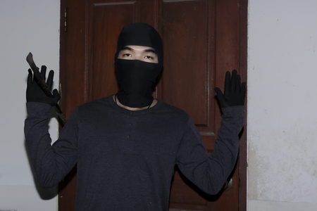 Thief with black balaclava raising hands up to the police. Catch burglar concept.