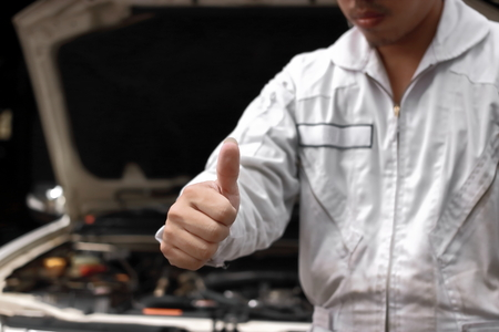 Selective focus on hands of professional young mechanic man showing thumb up as sign of success with car in open hood at the garage background. Auto repair service. 版權商用圖片