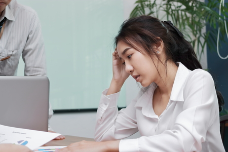 Depressed exhausted young Asian business woman suffering from severe depression between meeting in office. Stockfoto