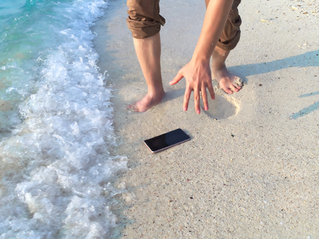 Hands of young Asian man dropping mobile smart phone on tropical sandy beach. Accident and insurance electronic equipment concept