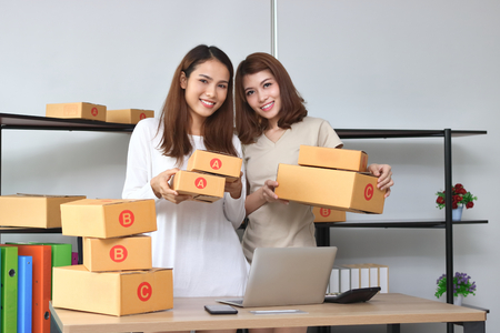 Cheerful Asian entrepreneur owner women looking confident at home office. Online start up business.