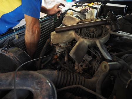 Mechanic man in uniform repairing car in garage. Auto repair service. 版權商用圖片