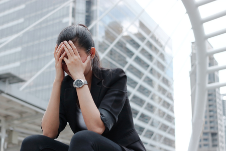 Depressed stressed young Asian business woman covering face with hands suffering from trouble Banco de Imagens