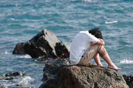 Depressed upset young Asian man covering face with hands sitting on the rock of sea shore.