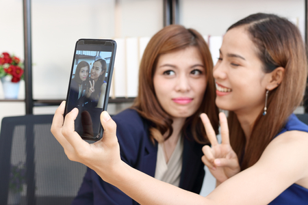 Cheerful young Asian business women taking a picture or selfie together in office. Stock Photo