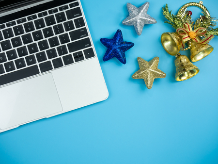 Top view of laptop and decorations on blue isolated background. Christmas and New Year holiday concept