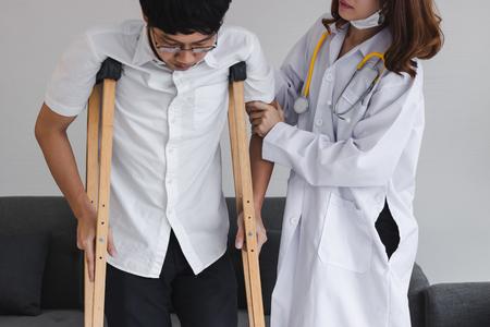 Physique femme médecin aidant le patient avec des béquilles dans le bureau de l'hôpital. Banque d'images
